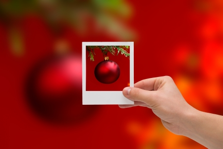 Holding Instant photo on a christmas ball background  Stock Photo