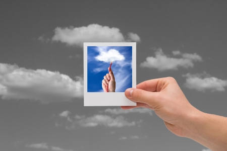 Holding instant cloud photo on a black sky background  photo