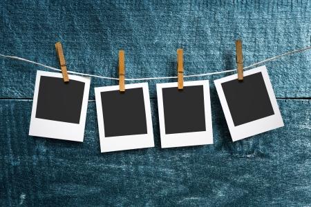 załączyć: cztery papier fotograficzny dołączyć do liny z ubrania pinów na tle drewniane Zdjęcie Seryjne