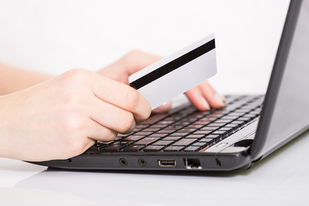 entering information: Hands entering credit card information into a laptop Stock Photo