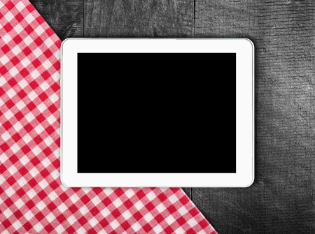 Tablet, tablecloth textile texture on wooden table background photo