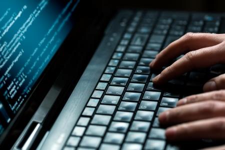 teclado: Hacker usando un mont�n de port�tiles de d�gitos en la pantalla del ordenador Foto de archivo