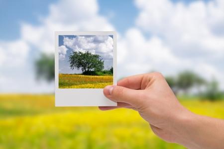 Sosteniendo foto instantánea sobre un fondo otoño Foto de archivo