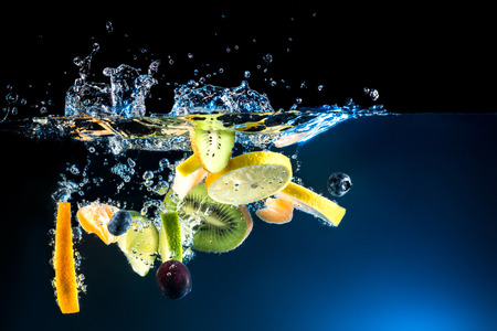 Splashing fresh fruit on water on black background photo
