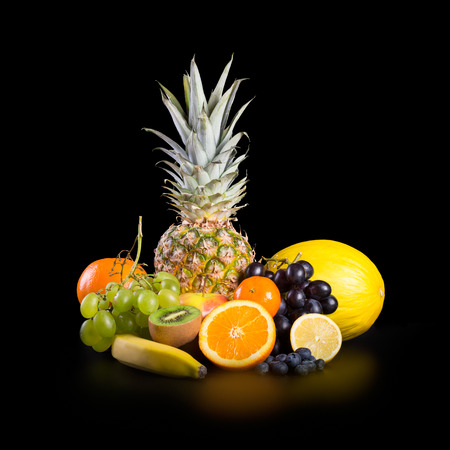 Assortment of exotic sweet fruits isolated on black background photo