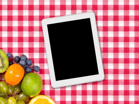 tablet and fruit on tablecloth textile photo