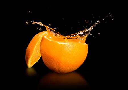 Orange juice splashing isolated on black photo