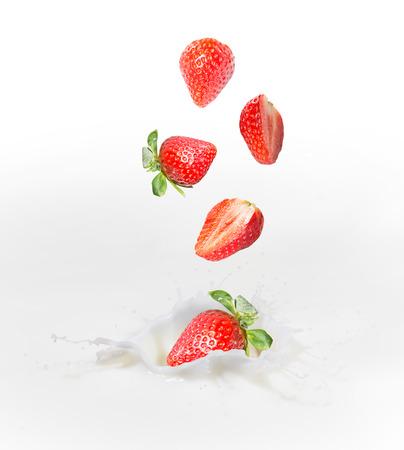 Strawberry falling into splashing milk or yogurt  Reklamní fotografie