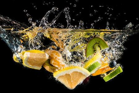 agribusiness: Splashing fresh fruit on water isolated on black