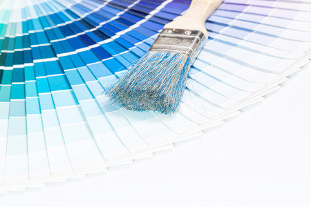 Paintbrushes and blue color samples over white background  photo