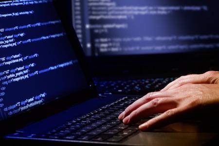 Hacker met behulp van laptop Veel cijfers op het computerscherm