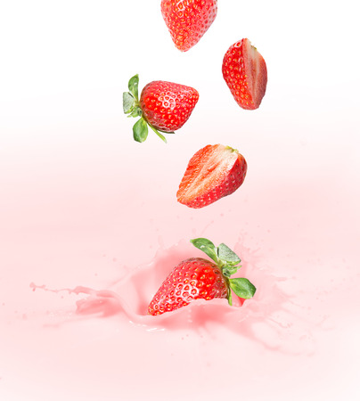 Strawberry falling into splashing milk or yogurt  photo