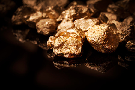 Gouden goudklompjes die op zwarte achtergrond Stockfoto