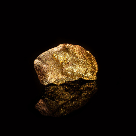 tough luck: Gold nugget isolated on black background