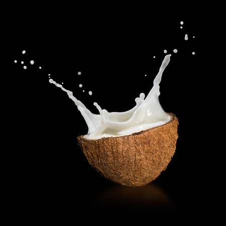 Coconuts with milk splash on black background