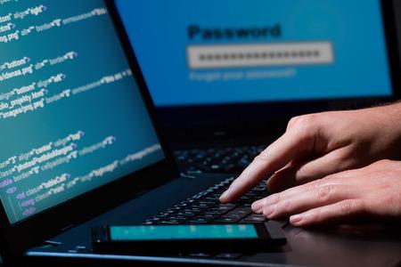 Hacker usando un montón de portátiles de dígitos en la pantalla del ordenador Foto de archivo - 27544250