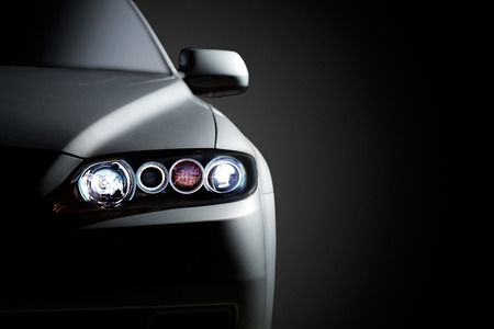 headlights: Gray modern car closeup on black background  Stock Photo