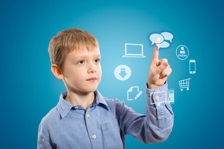 pointing device: Boy accessing futuristic entertainment applications from the cloud computing interface Stock Photo