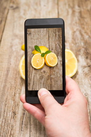 Hands taking photo of fruits on wooden background  photo