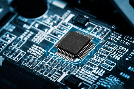 Closeup of electronic circuit board with processor on blue tone