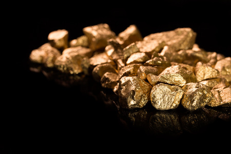 unearth: Gold nuggets isolated on black background