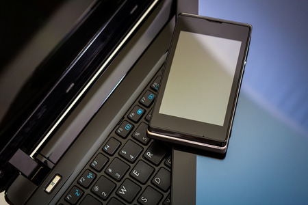 Closeup picture of a keyboard with a phone and tablet lying above photo