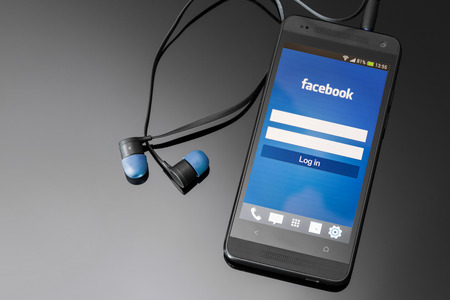 mobile headsets: BELCHATOW, POLAND - APRIL 06, 2014: Facebook application on smart phone screen. Editorial