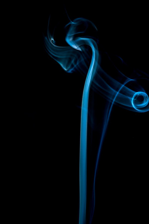 smoke effect: Abstract blue smoke swirls on black background.