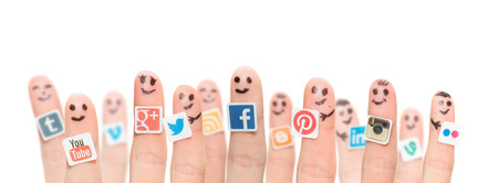 medias: BELCHATOW, POLAND - AUGUST 31, 2014: Happy group of finger smileys with popular social media logos printed on paper and stuck to the fingers.