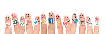 BELCHATOW ポーランド - 2014 年 8 月 31 日: 幸せなグループ、人気のソーシャル メディアのロゴと指スマイリーの紙に印刷し、指に立ち往生しています 報道画像