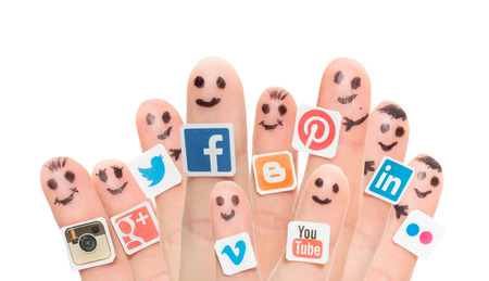 printed media: BELCHATOW, POLAND - AUGUST 31, 2014: Happy group of finger smileys with popular social media logos printed on paper and stuck to the fingers.