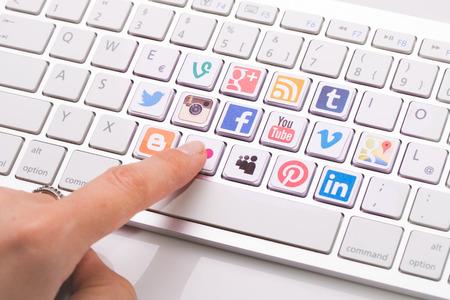 BELCHATOW, Polen - 31 augustus 2014: Mannelijke hand te wijzen op de belangrijkste met een social media logo collectie geprint en geplaatst op moderne toetsenbord van de computer.