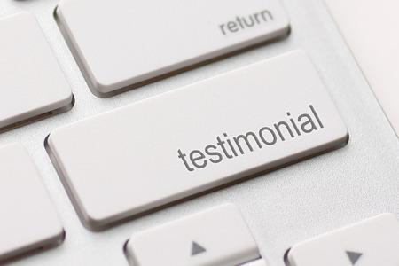 endorsement: Testimonial button key on white keyboard.