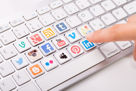 BELCHATOW, POLAND - AUGUST 31, 2014: Male hand pointing on key with a social media logotype collection printed and placed on modern computer keyboard. 에디토리얼