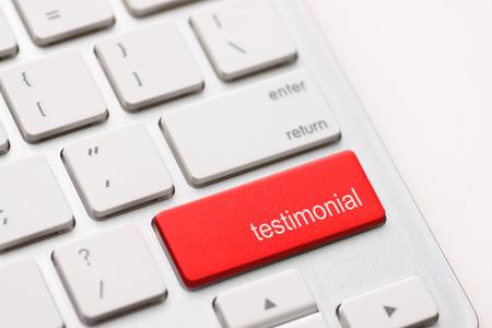 credentials: Testimonial button key on white keyboard.