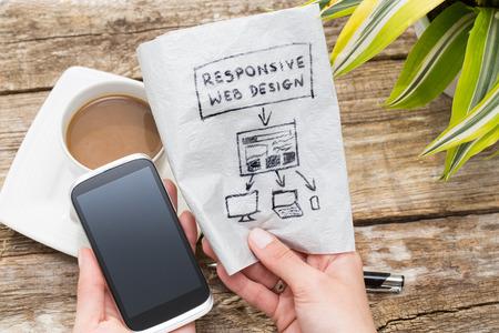 Web designer holding a blueprint of a new mobile application. Responsive web design concept. Stock Photo