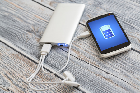 electric cell: Phone charging with energy bank. Stock Photo