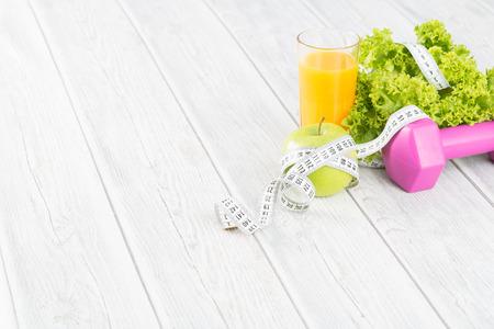 Conceito de fitness com halteres e alimentos saudáveis.