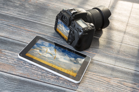 dslr: DSLR camera and tablet on a wooden table.