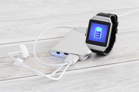 Smart watch charging with energy bank. Smartwatch concept.