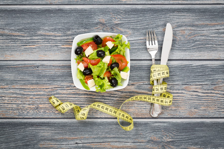 Fitness salad and measuring tape on rustic wooden table.