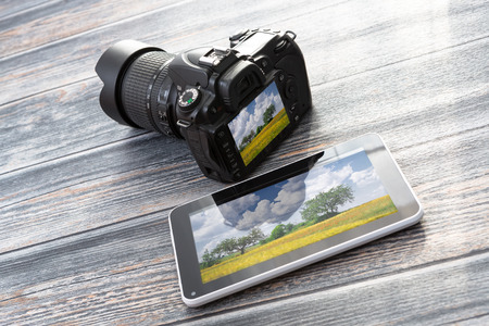 dslr camera: DSLR camera and tablet on a wooden table.