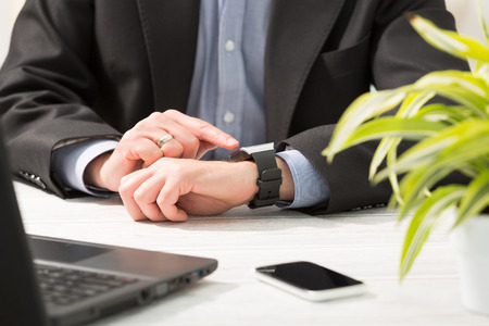 smart man: Businessman uses smart watch and phone. Smartwatch concept.