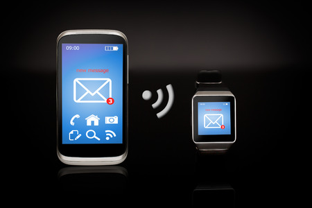 phone the clock: Modern internet smart watch and smartphone on black background.