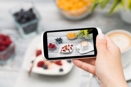 blogs: Woman taking a photo of breakfast with smartphone.