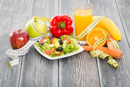 Fitness salade en meetlint op rustieke houten tafel.