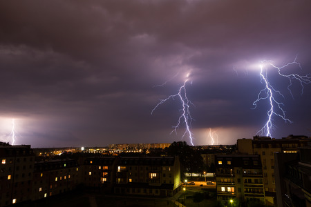 weather  thunder: Clouds and thunder lightnings and storm over city. Stock Photo