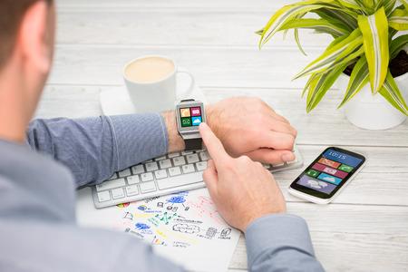 Homme d'affaires utilise montre intelligente et téléphone. Smartwatch notion.