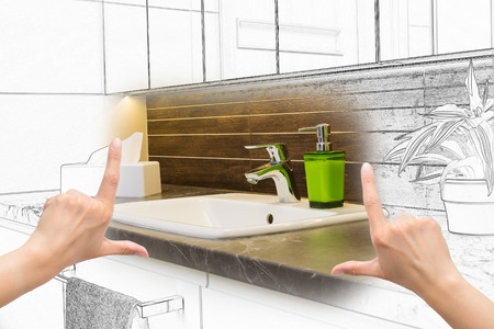 Female hands framing custom bathroom design. Combination drawing and photo.