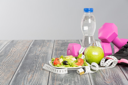Fitness equipment and healthy nutrition on wood background.
